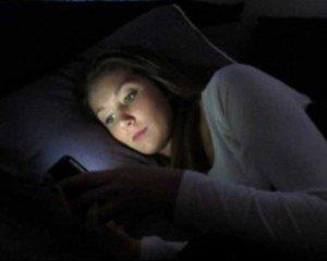 vrouw met telefoon in bed